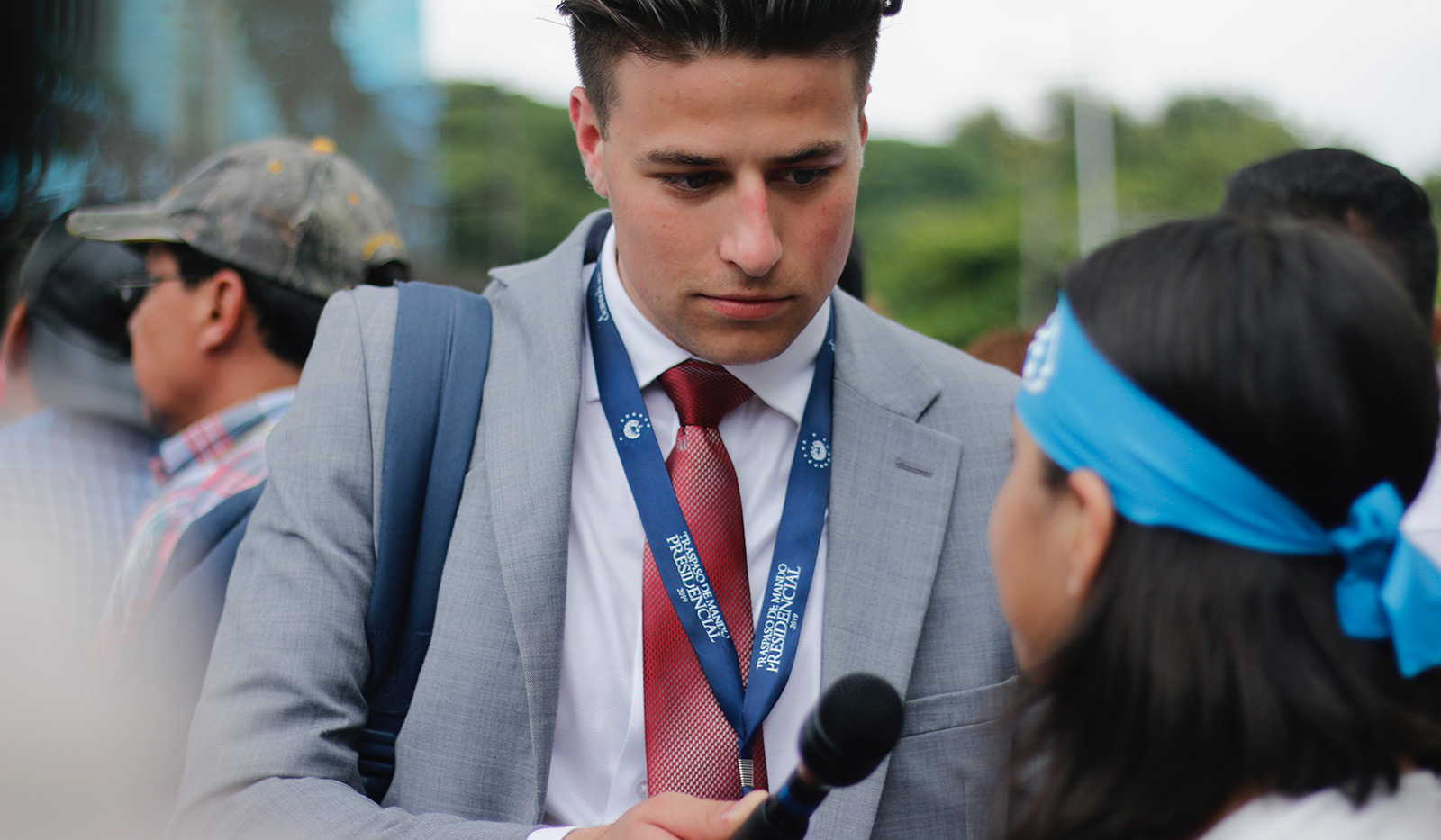 Male student journalism holding a microphone up to someone he interviewed